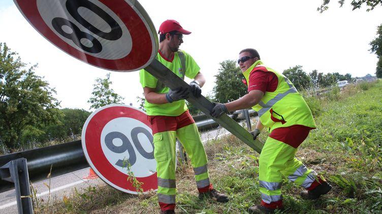 Des agents changent les panneaux de 90km/h en 80km/h en juin 2018. (HERVE KIELWASSER / MAXPPP)