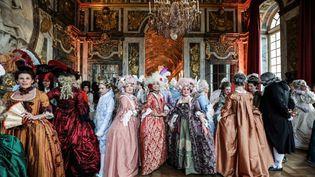 """En costumes d'époque, les participants des """"Fêtes Galantes"""" déambulent dans le château de Versailles (LUDOVIC MARIN / AFP)"""