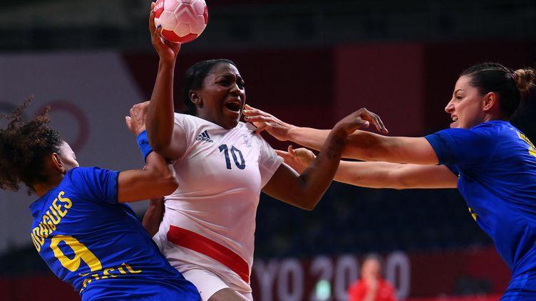 Grace Zaadi passe en force entre deux Brésiliennes lors du dernier match du groupe B à Tokyo, le 2 août. (FRANCK FIFE / AFP)