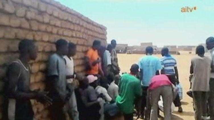 De jeunes Maliens se protègent lors de combats à Gao, le 24 mars 2013. (AITV)
