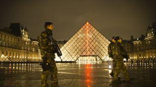 Des militaires du plan Vigipirate patrouillent devant la pyramide du Louvre, le 24 mars 2015. (JOEL SAGET / AFP)
