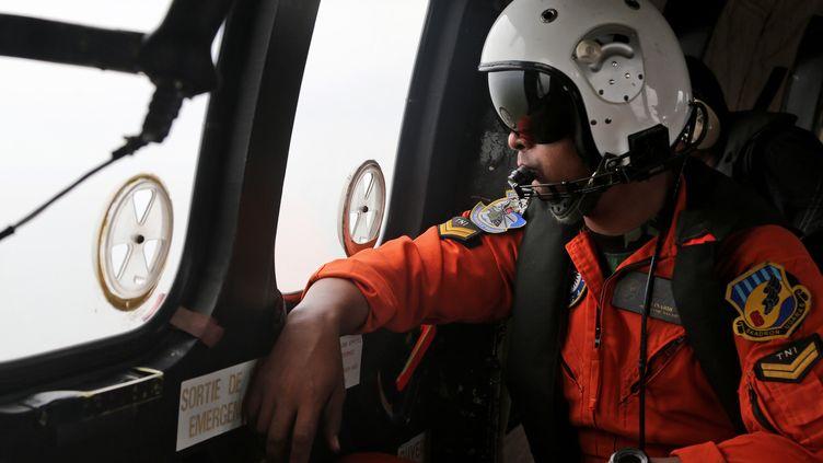 Un membre des forces aériennes indonésiennes le 5 janvier 2015, durant les opérations de recherche du vol QZ8501 d'AirAsia, disparu en mer de Java. (TATAN SYUFLANA / AFP)