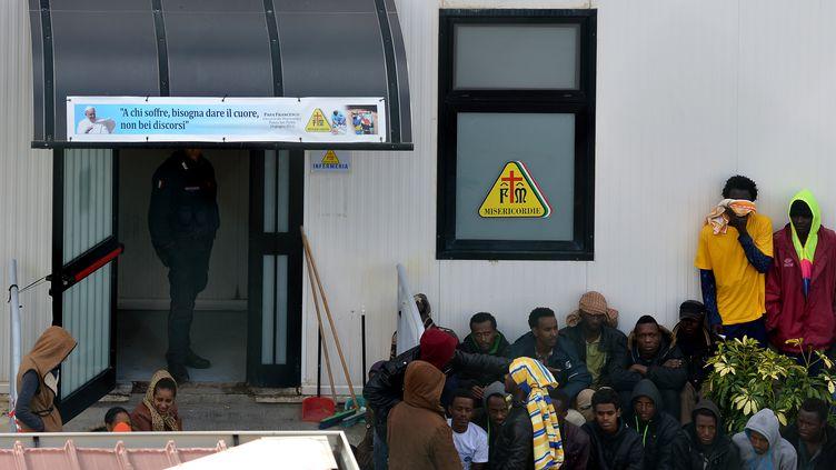 Des migrants attendent devant un camp de réfugiés, le 17 février 2015 à Lampedusa(Italie). (ALBERTO PIZZOLI / AFP)