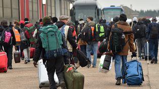 """Des migrants embarquent dans les bus pour quitter la """"jungle"""" de Calais le 24 octobre 2016 (PHILIPPE HUGUEN / AFP)"""