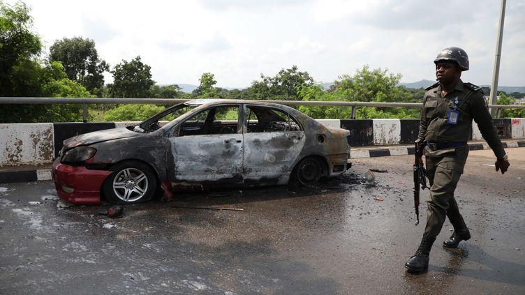 Un policier passe devant une voiture incendiée par des partisans d'Ibrahim Zakzaky, un dirigeant emprisonné du Mouvement islamique du Nigeria (MIN), près du bâtiment de l'Assemblée nationale à Abuja, la capitale du Nigeria, le 9 juillet 2019. (KOLA SULAIMON / AFP)