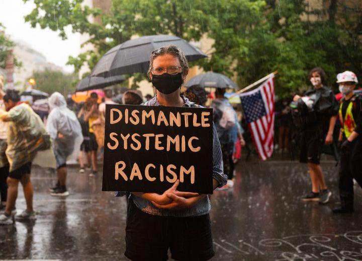 """Une personne porte une pancarte contre le """"racisme systémique"""" près de la Maison Blanche à Washington (Etats-Unis), lors d'une manifestation contre les violences policières et le racisme, le 5 mai 2020. (ZACH D ROBERTS / NURPHOTO)"""