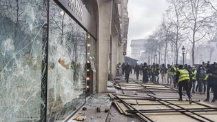 """Des """"gilets jaunes"""" devant la vitrine brisée d'un magasin sur les Champs-Elysées, le 16 mars 2019 à Paris. (AMAURY CORNU / HANS LUCAS / AFP)"""