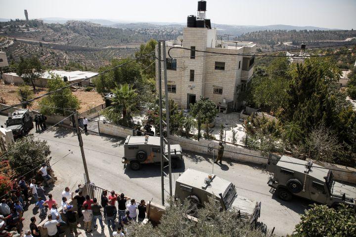Des véhicules militaires et des soldats israéliens sont déployés àBeit Surik, village palestinien situé en face de la colonie où s'est déroulée l'attaque. Ils encerclent l'habitation d'un Palestinien. (ABBAS MOMANI / AFP)