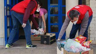 Des bénévoles de la fondation Caritas déposent des cartons de nourriture et de produits de première nécessité à l'entrée d'un immeuble, à Burgos (Espagne), le 26 mars 2020. (CESAR MANSO / AFP)