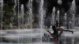 Des enfants se rafraîchissent dans une fontaine à Nice (Alpes-Maritimes), le 27 juin 2019. (ERIC GAILLARD / REUTERS)