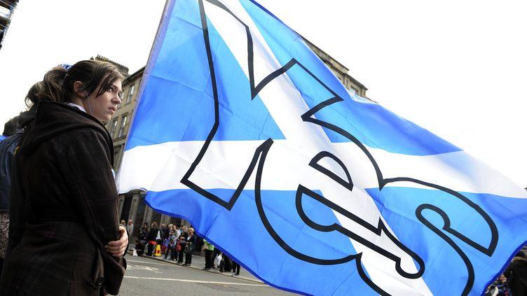 """Une femme tient un drapeau écossais avec l'inscription """"Oui"""", en faveur de l'indépendance de l'Ecosse, le 15 août 2014, à Glasgow. (ANDY BUCHANAN / AFP)"""
