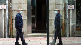 Un passant portant un masque de protection dans une rue de Pontevedra, en Galice(Espagne), le 4 mai 2020. (MIGUEL RIOPA / AFP)