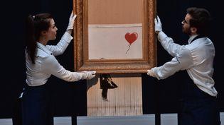 """Des employés de Sotheby's dévoilent """"Girl with balloon"""" de Banksy partiellement autodétruite et rebaptisée """"Love is in the bin"""", le 12 octobre 2018 à Londres."""
