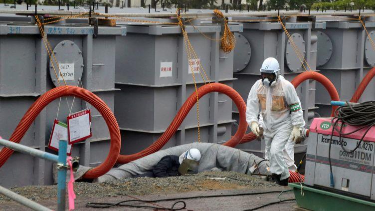 Un employé de Tepco (Tokyo Electric Power) travaillant sur les cuves de stockage des eaux contaminées, le 12 juin 2013, à Fukushima (Japon). (NOBORU HASHIMOTO / AFP)