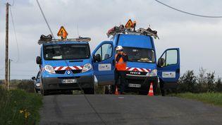 Des agents du réseau ERDF s'affairent pour réparer les lignes endommagées par la tempête, à Pluzunet (Côtes-d'Armor), le 28 octobre 2013. (CHARLY TRIBALLEAU / AFP)