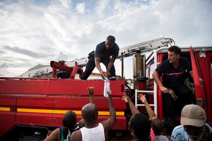 Après le passage de l'ouragan Irma, des pompiers distribuent de l'eauà des habitants du Marigot, le 10 septembre 2017, sur l'île de Saint-Martin. (MARTIN BUREAU / AFP)