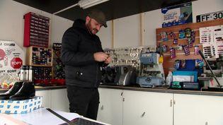 Privé de sa boutique, Davis Paris, cordonnier, dépanne ses clients sur le parking d'un supermarché. (S. Gérain / France Télévisions)