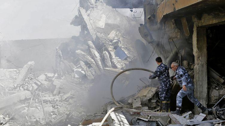 Des soldats syriens inspectent un bâtiment en ruines situé dans le quartier de Barzeh, dans le nord de Damas, samedi 14 avril 2018. (LOUAI BESHARA / AFP)