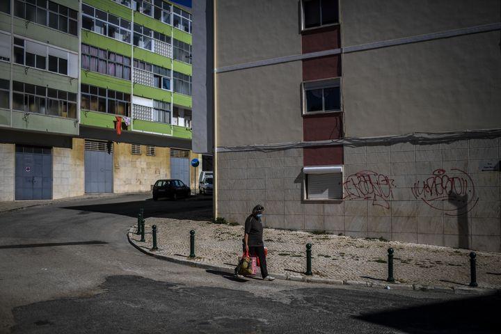 Une femme équipée d'un masque porte ses provisions à Loures, dans la banlieue de Lisbonne (Portugal), le 30 juin 2020. (PATRICIA DE MELO MOREIRA / AFP)