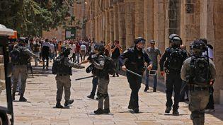 Les forces de sécurité israéliennes se battent avec de jeunes Palestiniens dans l'enceinte de la mosquée al-Aqsa à Jérusalem, le troisième site le plus sacré de l'Islam, le 14 mai 2021. (AHMAD GHARABLI / AFP)