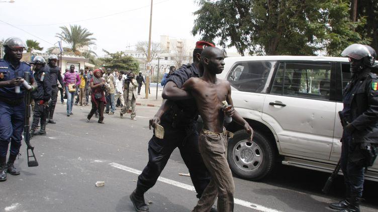 Un manifestant de l'opposition arrêté mercredi 15 février à Dakar, au Sénégal. (MAMADOU TOURE BEHAN / AFP)