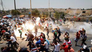 Des Palestiniens courent après des jets de gaz lacrymogène de la part des forces israéliennes, le 21 juillet 2017, dans une rue de Jérusalem. (AMMAR AWAD / REUTERS)
