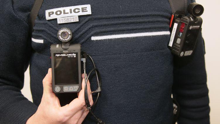 Un policier arbore deux caméras-piétons lors de l'inauguration du commissariat des Mureaux (Yvelines), le 8 avril 2016. (JACQUES DEMARTHON / AFP)