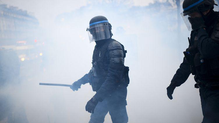 Un policier tenant une matraque à la main entouré de fumée de gaz lacrymogène lors d'une manifestation à Paris, le 30 janvier 2021. (CHRISTOPHE ARCHAMBAULT / AFP)