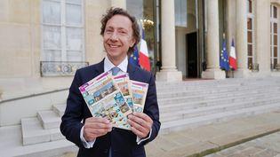 L'animateur Stéphane Bern pose avec des tickets du loto du patrimoine devant l'Elysée le 31 mai 2018. (LUDOVIC MARIN / AFP)