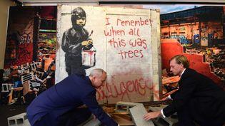 """La peinture murale deBanksy """"I remember when all this was trees"""", mise en scène par Martin Nolan (à gauche) et Michael Doyle, de la maison d'enchères Julien, en vue de sa vente à Los Angeles (23 septembre 2015)  (Frédéric J. Brown / AFP)"""