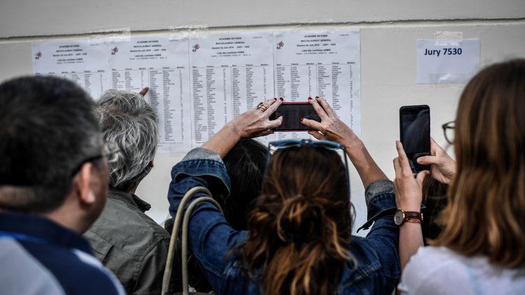 Des parents prennent en photo les résultats du baccalauréat devant le lycée Fresnel à Paris, le 5 juillet 2019. (STEPHANE DE SAKUTIN / AFP)