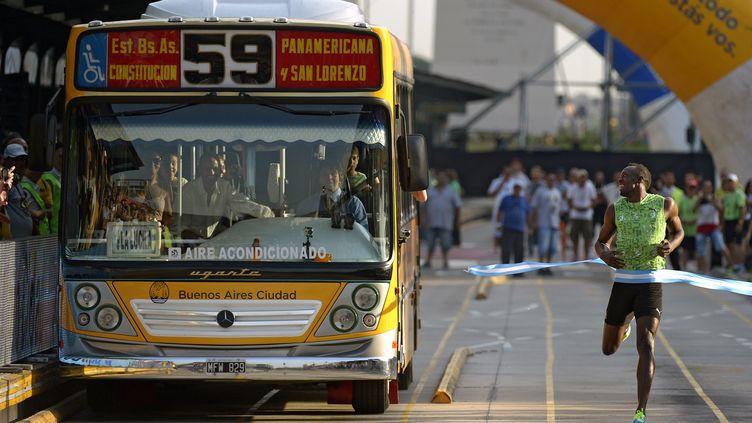 Usain Bolt court un 100 m contre un autobus, à Buenos Aires (Argentine), le 14 décembre 2013. (JUAN MABROMATA / AFP)