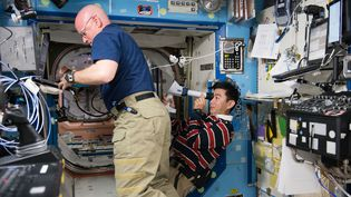 L'astronaute américain Scott Kelly (à gauche) et le JaponaisKimiya Yui, en plein travail, dans la Station spatiale internationale, le 5 août 2015. (NASA / AFP)