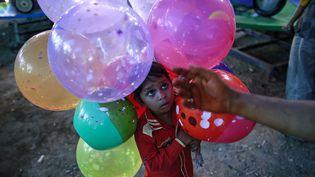 Un petit garçon âgé de cinq ans aide son père vendeur de ballons à Bombay (Inde), le 8 décembre 2014. (DANISH SIDDIQUI / REUTERS)
