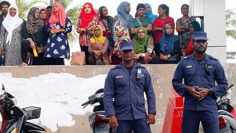 Des policiers maldiviens montent la garde près du siège du principal parti d'opposition, le 6 février 2018 à Malé, au lendemain de l'instauration de l'état d'urgence. (REUTERS)