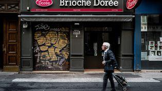 Une habitant passe samedi 25 mai devantla boulangerie Brioche dorée, rue Victor-Hugo à Lyon, où a eu lieu l'explosition la veilled'un colis piégé, qui a fait 13 blessés. (JEFF PACHOUD / AFP)