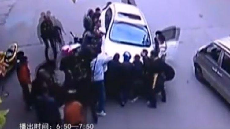 Capture d'écarn montrant les bons samaritains qui soulèvent la voiture pour libérer unefemme qui se trouve en-dessous, dansla province du Zhejiang (Chine) (STERLIN TV / YOUTUBE)