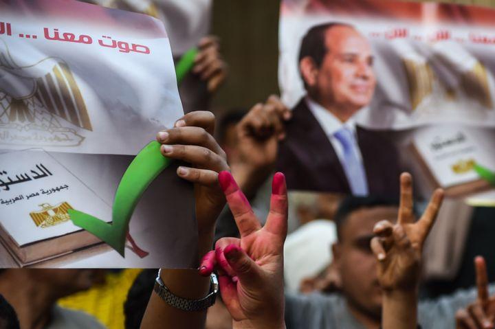 Dans un bureau de vote de Menoufia (nord de l'Egypte), des électeurs égyptiens montrent leurs mains prouvant qu'ils ont participé au référendum le 22 avril 2019.En arrière plan, la photo du président Abdel Fattah al-Sissi (MOHAMED EL-SHAHED / AFP)