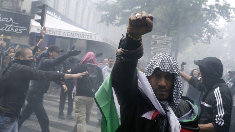 Un manifestant pro-palestinien lève le poing pendant un défilé de soutien à la population gazaouie, le 13 juillet à Paris. (KENZO TRIBOUILLARD / AFP)