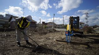 Des travailleurs chargés de la décontamination, retire du sol irradié à Namie, à huit kilomètres de la centrale nucléaire de Fukushima (Japon), le 24 février 2016. (FRANCK ROBICHON / EPA)