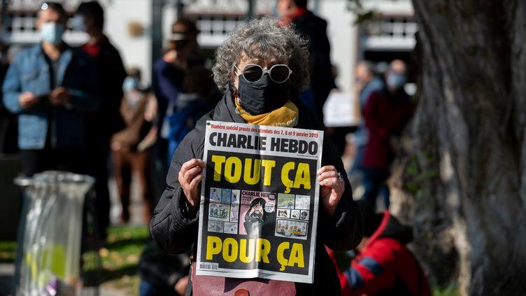 """Une femme avec un exemplaire de l'hebdomadaire satirique """"Charlie Hebdo"""", lors d'un rassemblement à Nantes,en hommage à Samuel Paty, le 18 octobre 2020. (ESTELLE RUIZ / HANS LUCAS / AFP)"""