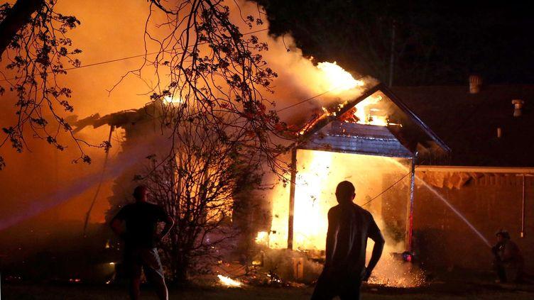 Une personne observe la scène de l'explosion d'une usine agricole, où interviennent les pompiers, le 17 avril 2013, à West (Texas, Etats-Unis). (ROD AYDELOTTE / AP / SIPA)