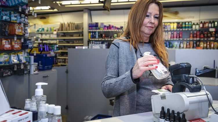 Une pharmacienne vendant un flacon de gel hydroalcoolique dans une pharmacie, à Amsterdam. (DINGENA MOL / ANP)