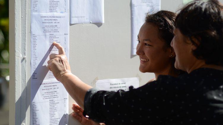 Ranitea Gobrait avec sa mère devant le panneau d'affichage des résultats du baccalauréat à Papeete (Polynésie française), le 6 juillet 2018. (MIKE LEYRAL / AFP)