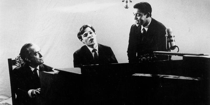 Le Vinícius lyrique, musical, musicien, avec Tom Jobim au piano, en compagnie du chanteur Agostinho dos Santos au début des années 60 à Rio de Janeiro.  (Archive / Agência Estado / AFP)
