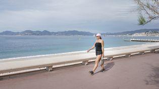 Une passante profite du beau temps sur le front de mer, le 30 avril 2020, à Cannes (Alpes-Maritimes). (ARIE BOTBOL / HANS LUCAS / AFP)