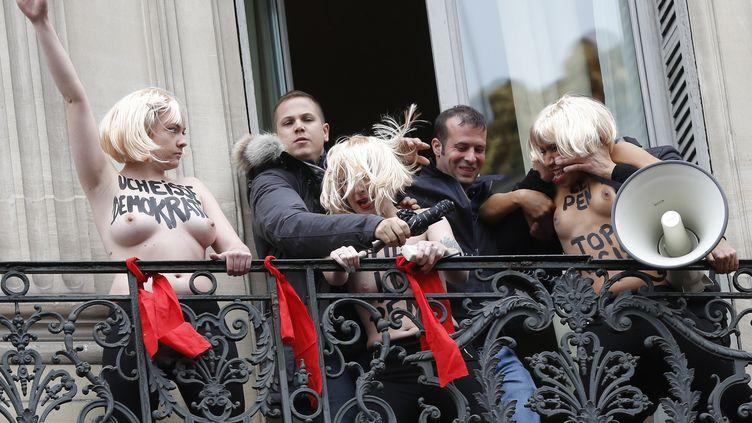Des hommes évacuent violemment des militantes Femen, après l'interruption du discours de Marine Le Pen, le 1er mai 2015, à Paris. (THOMAS SAMSON / AFP)