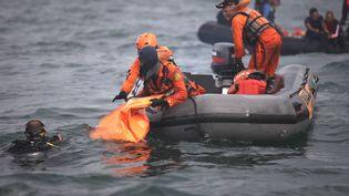 Des plongeurs remontent à la surface des sacs remplis de débris et de restes humains après la disparition du Boeing 737-500 de Sriwijaya Air, le 11 janvier 2021 au large de Jakarta. (DEMY SANJAYA / AFP)