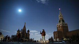 Une femme utilise son smartphone sur la place rouge à Moscou (Russie), tandis que la tour Spasskaya du Kremlin et la Cathédrale Basile-le-Bienheureux sont éteintes pour l'Eeath Hour, le 27 mars 2021. (PAVEL GOLOVKIN / AP)