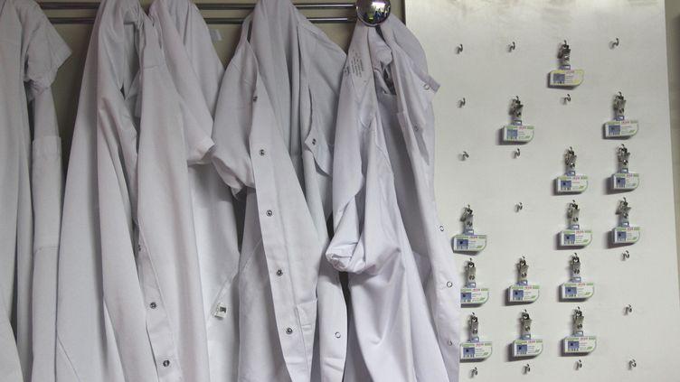 Blouses suspendues à une patère à l'entrée du service de radiologiedu CHU Gabriel Montpied à Clermont-Ferrand. (GÉRALDINE MARCON / RADIOFRANCE)